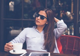A woman in sunglasses sitting in a cafe and drink coffee