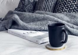 Bok som handlar om bröllop och bredvid är det en kaffekop och en filt