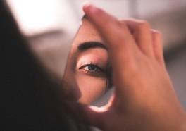 Influencer om håller i en liten spegel som visar en del av hennes ansikte