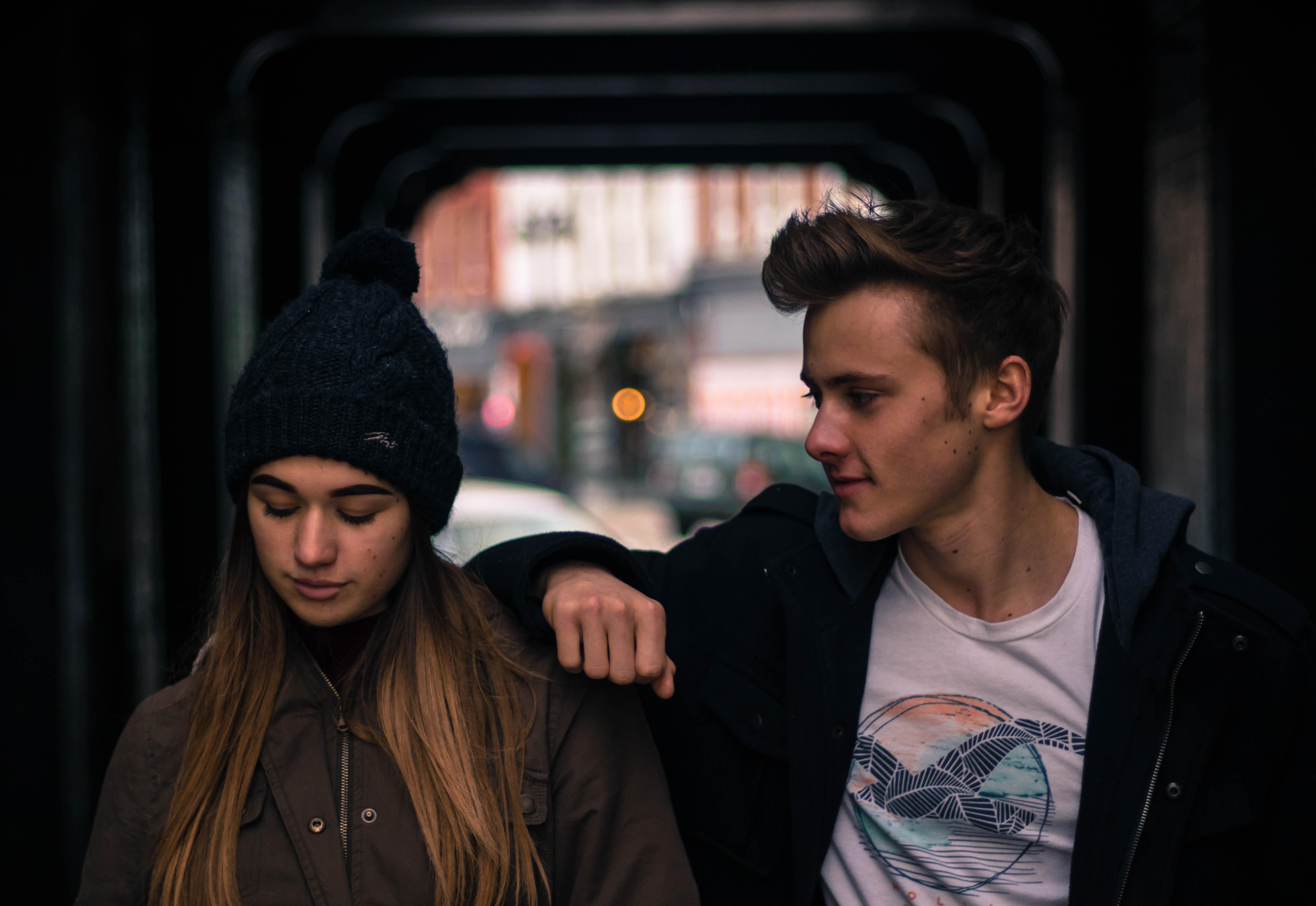 En tjej och en kille står  bredvid varandra i tunnel och poserar
