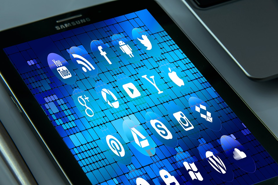 En tablet med blå bakgrund som visar en massa sociala medier ikoner och andra appar
