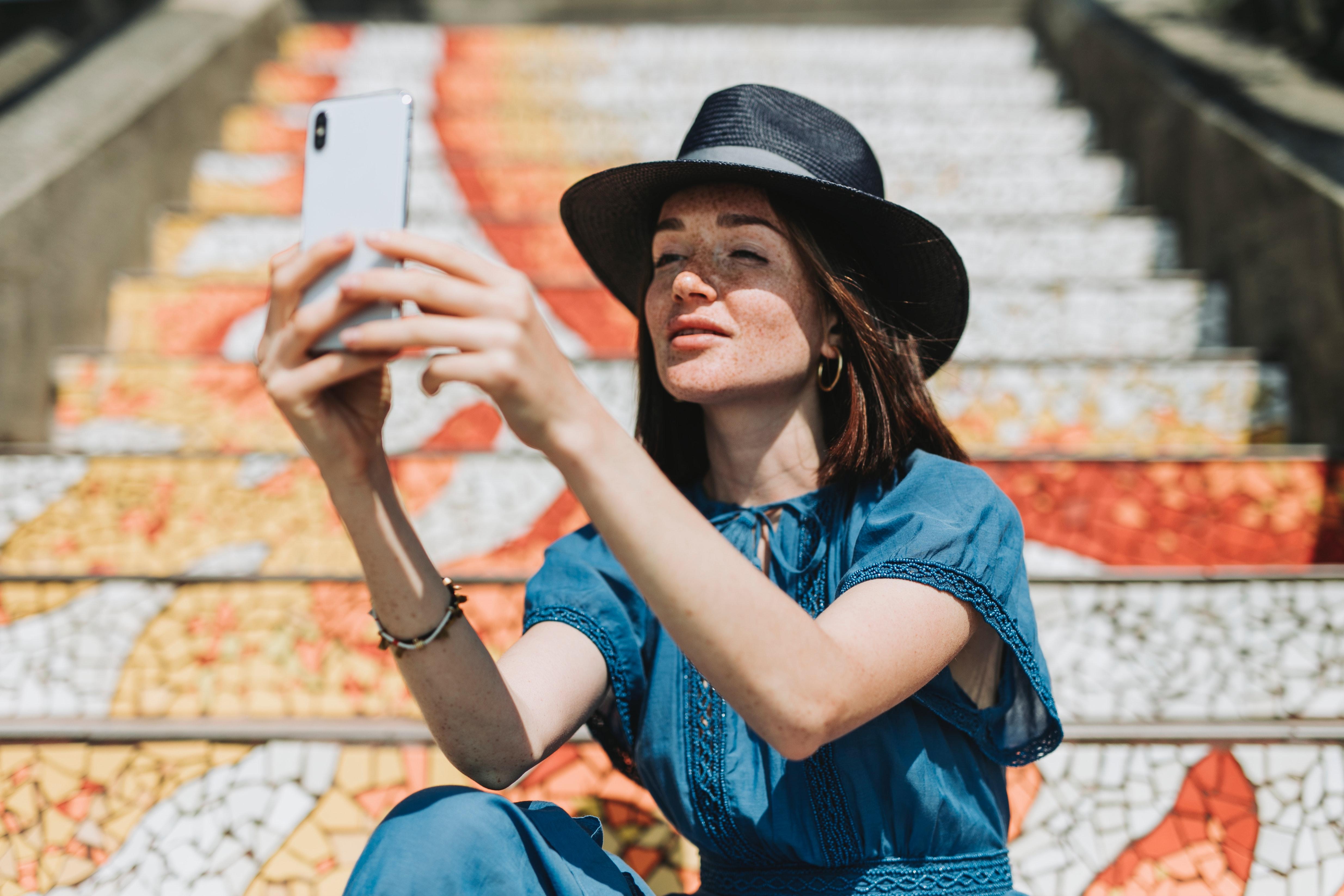En tjej som sitter i en trappa och tar en selfie