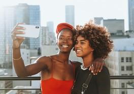 Två tjejer från instagram tar en selfie tillsammans i en storstad