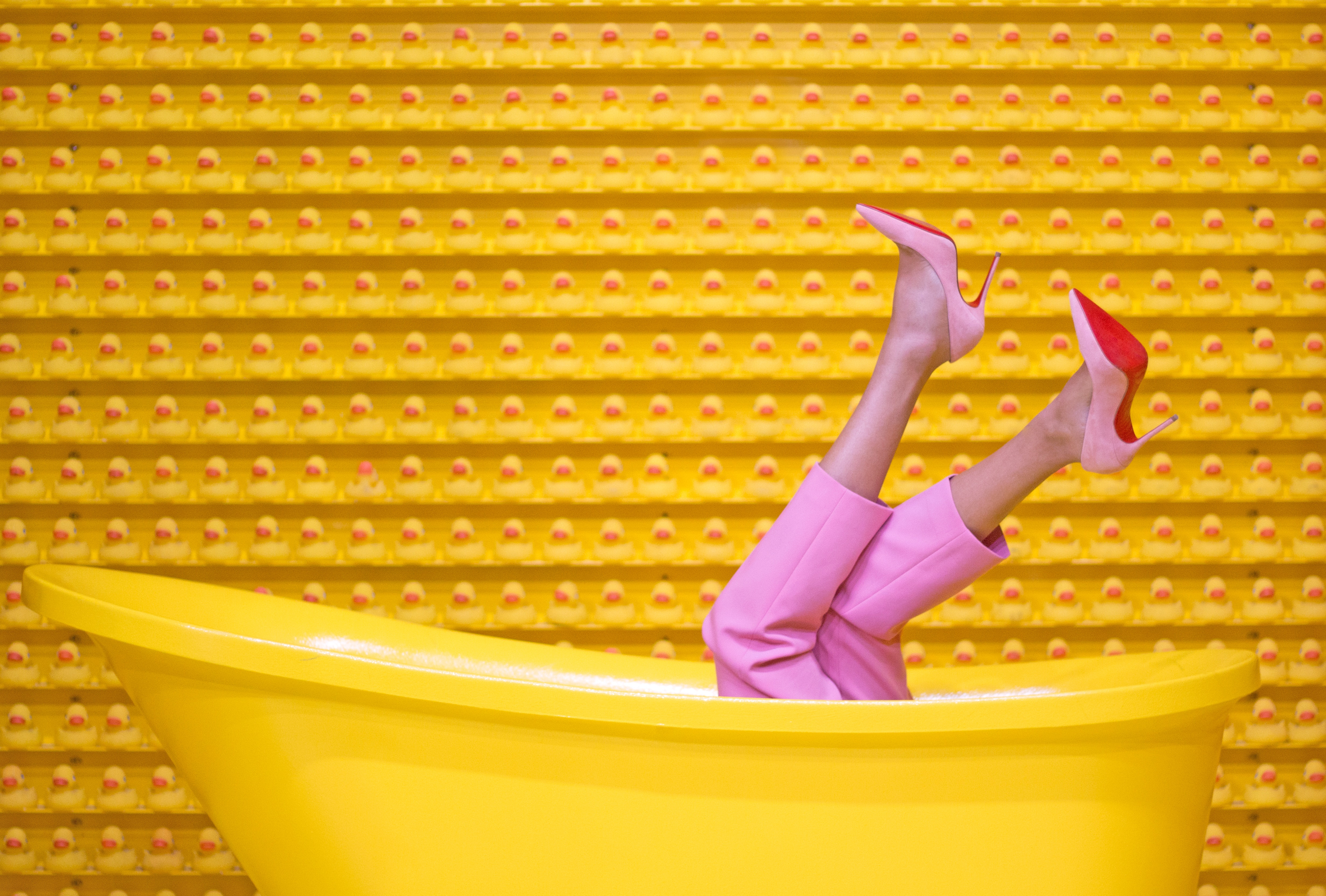 Women in pink clothes sit in a yellow bathtub in front of a yellow wall with red dots