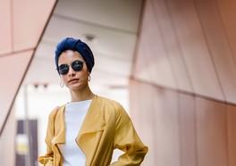 Influencer i trendiga kläder och glasögon poserar och kollar rakt in i kameran