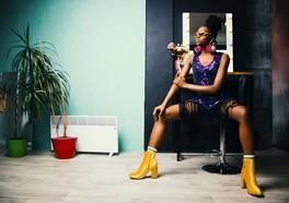 Influencer med solglasögon och gula klackar sitter på en stol och poserar framför en turkosa vägg