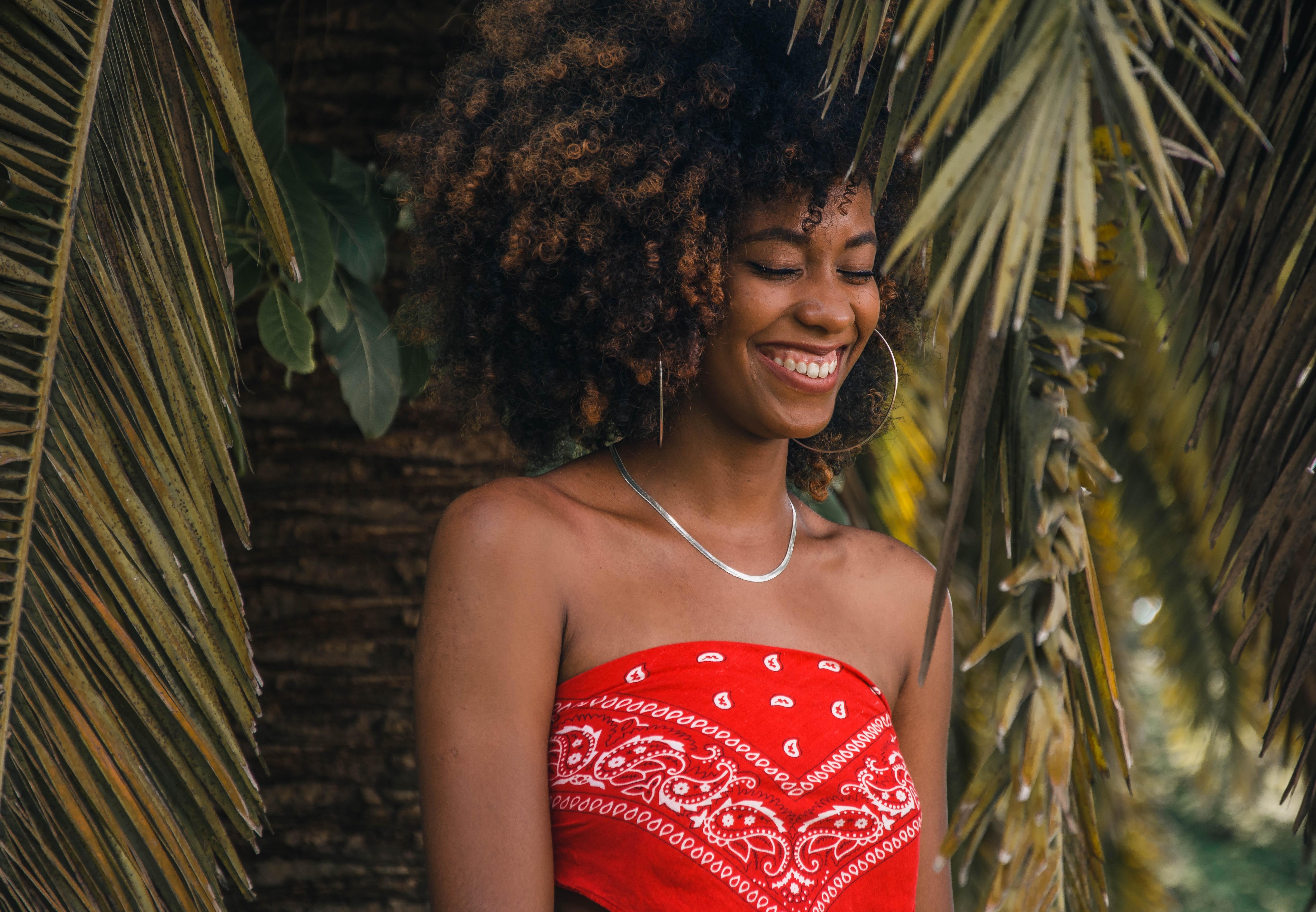 Tjej som ler och är sommarklädd poserar framför en palm