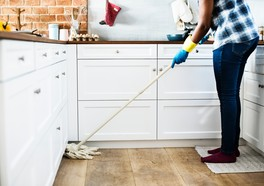 person holding a mop and cleaning in a white kitchen