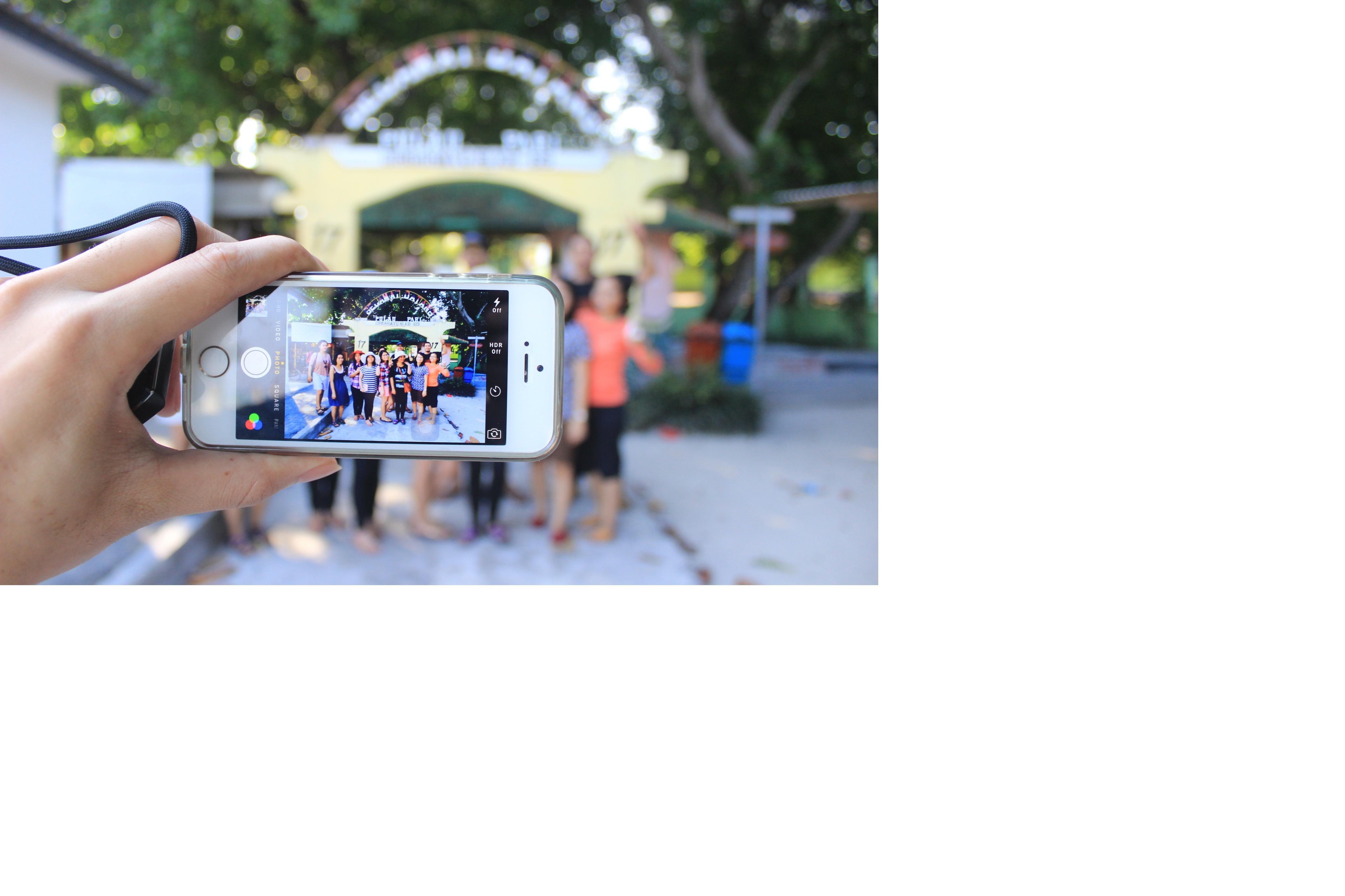 iPhone som tar foto på en grupp människor i en nöjespark