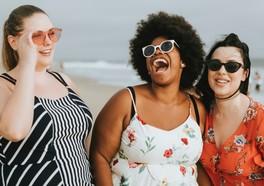 Tre influencers i solglasögon är på en strand skrattar tillsammans