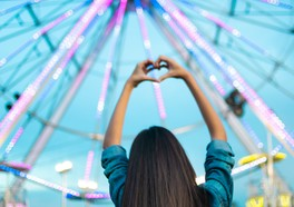 Tjej som gör ett hjärta med sina händer i en nöjespark