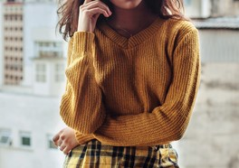En influencer i en gul tröja som poserar
