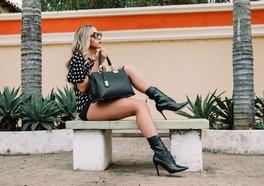 Tjej i svarta klackar och prickig blus poserar på en bänk med två palmer bredvid och en gulvägg