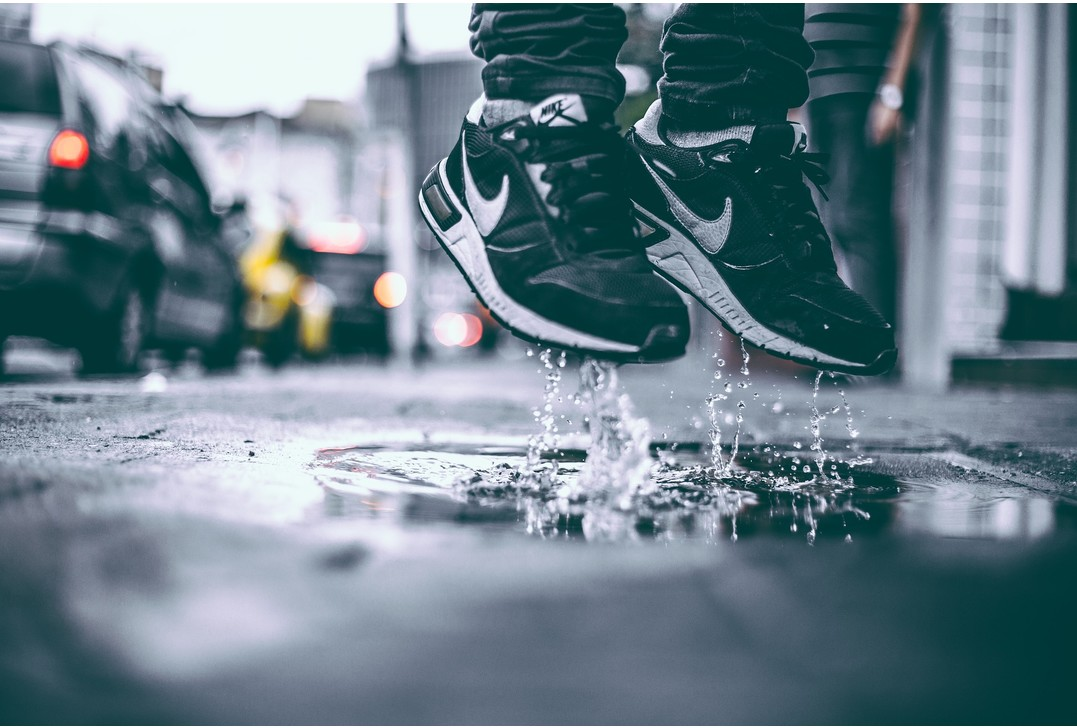 Person som har på sig Nike sneakers  och hoppar upp från en vattenpöl
