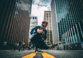 Kille i en keps som sitter ner på en gata i en storstad med en kamera i handen