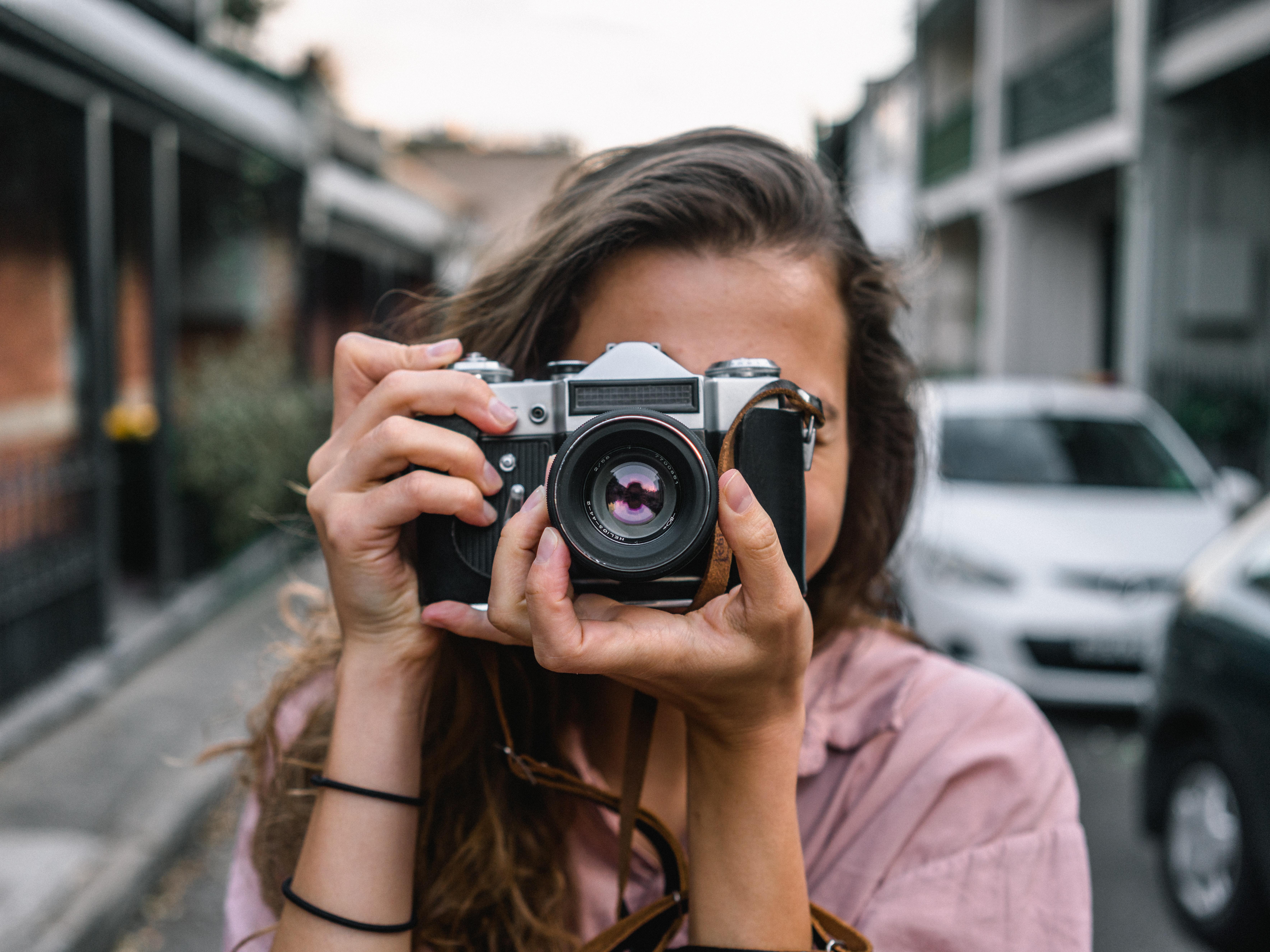 Tjej som håller i en kamera riktad mot skärmen och tar en bild