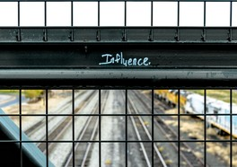 """On a handrail there is a text written """"influence"""" ,on bridge with train rails under"""