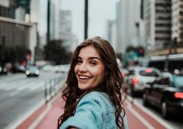Tjej som ler och som tar en selfie i en storstad