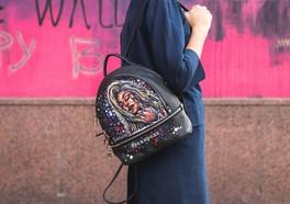 Kvinna som poserar framför en rosa vägg med en väska