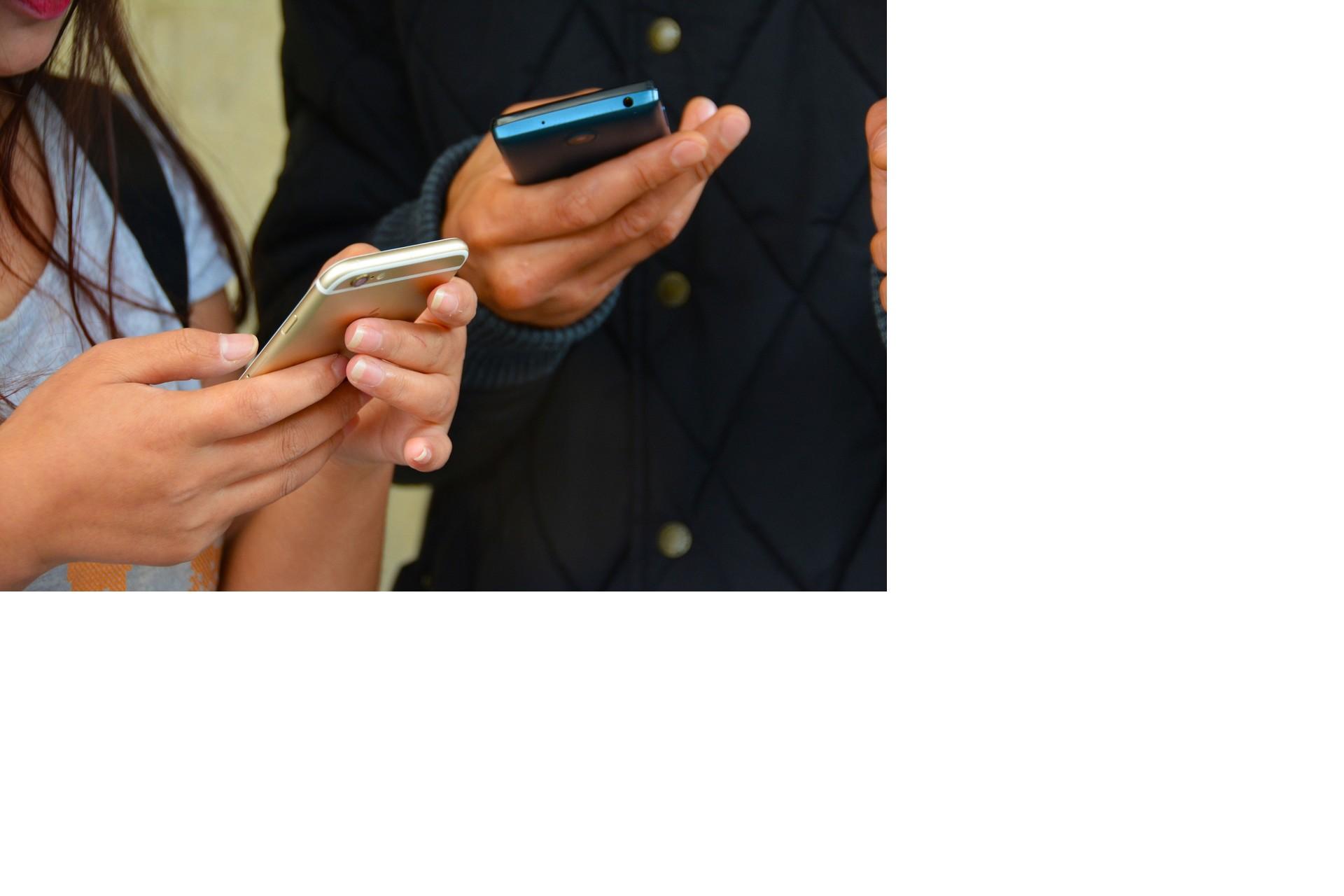 En tjej och kille håller och kollar på sina sociala medier i mobilerna