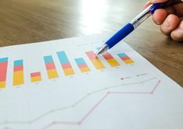 Person som håller i en penna och pekar på en graf på ett papper med en massa grafer