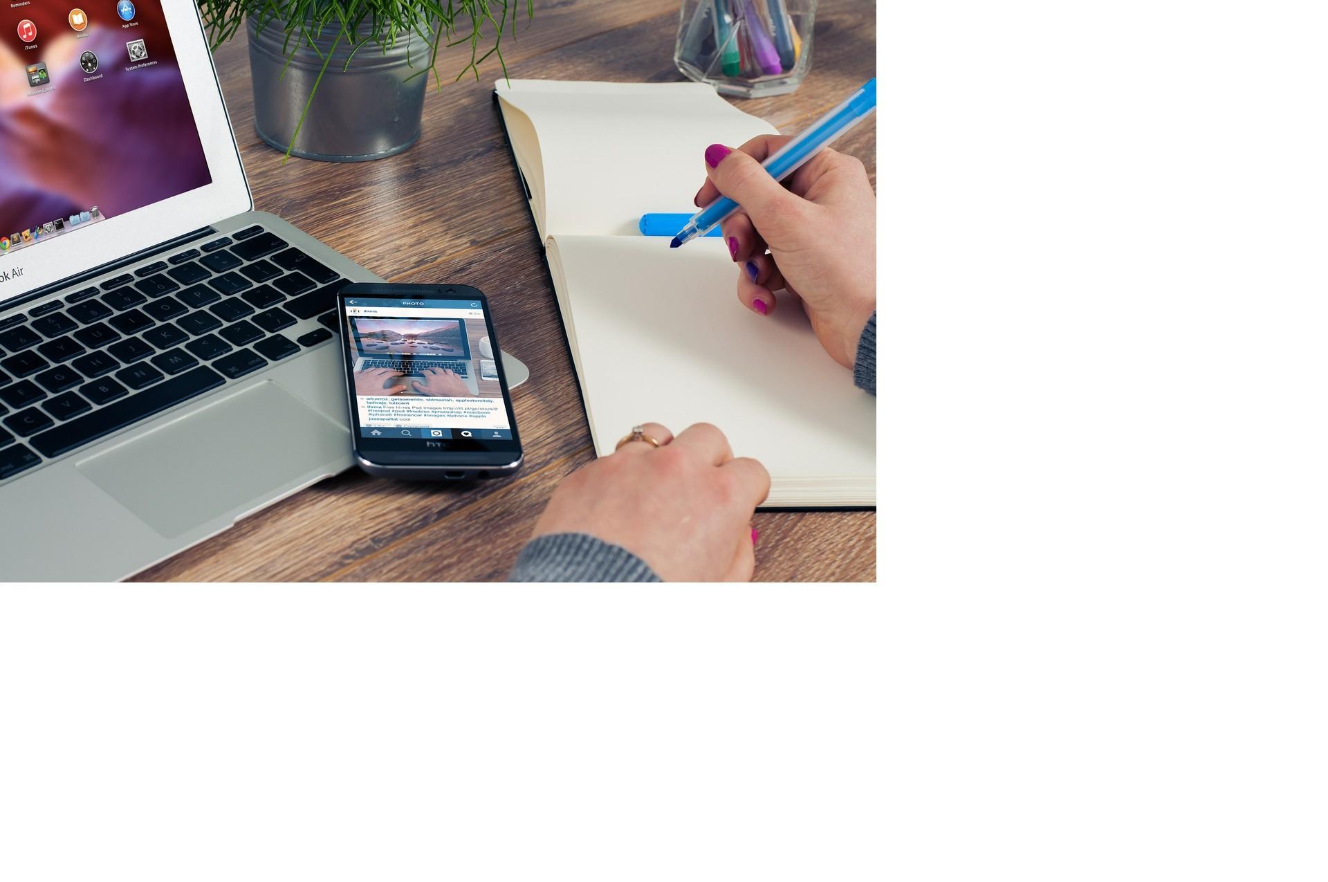Person som sitter vid ett skrivbord och gör anteckningar på ett block bredvid sin macbook och mobil