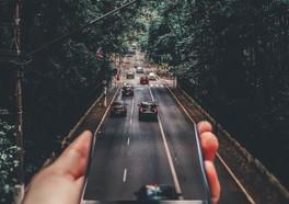 En hand som håller i en bilväg med bilar på med en korsning längre fram