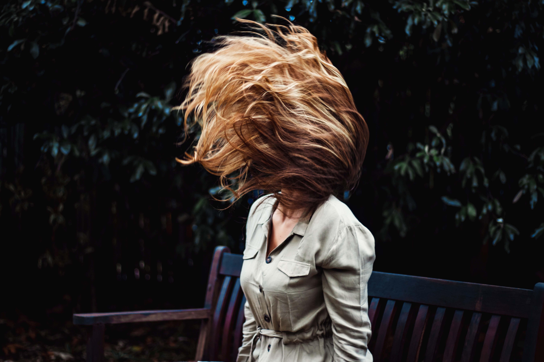 Tjej som viftar upp sitt hår i luften med gröna växter i bakgrunden