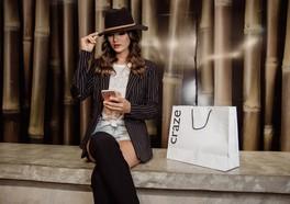 Tjej i hatt och kavaj som håller i sin mobil och har en shoppingpåse från craze brevid sig