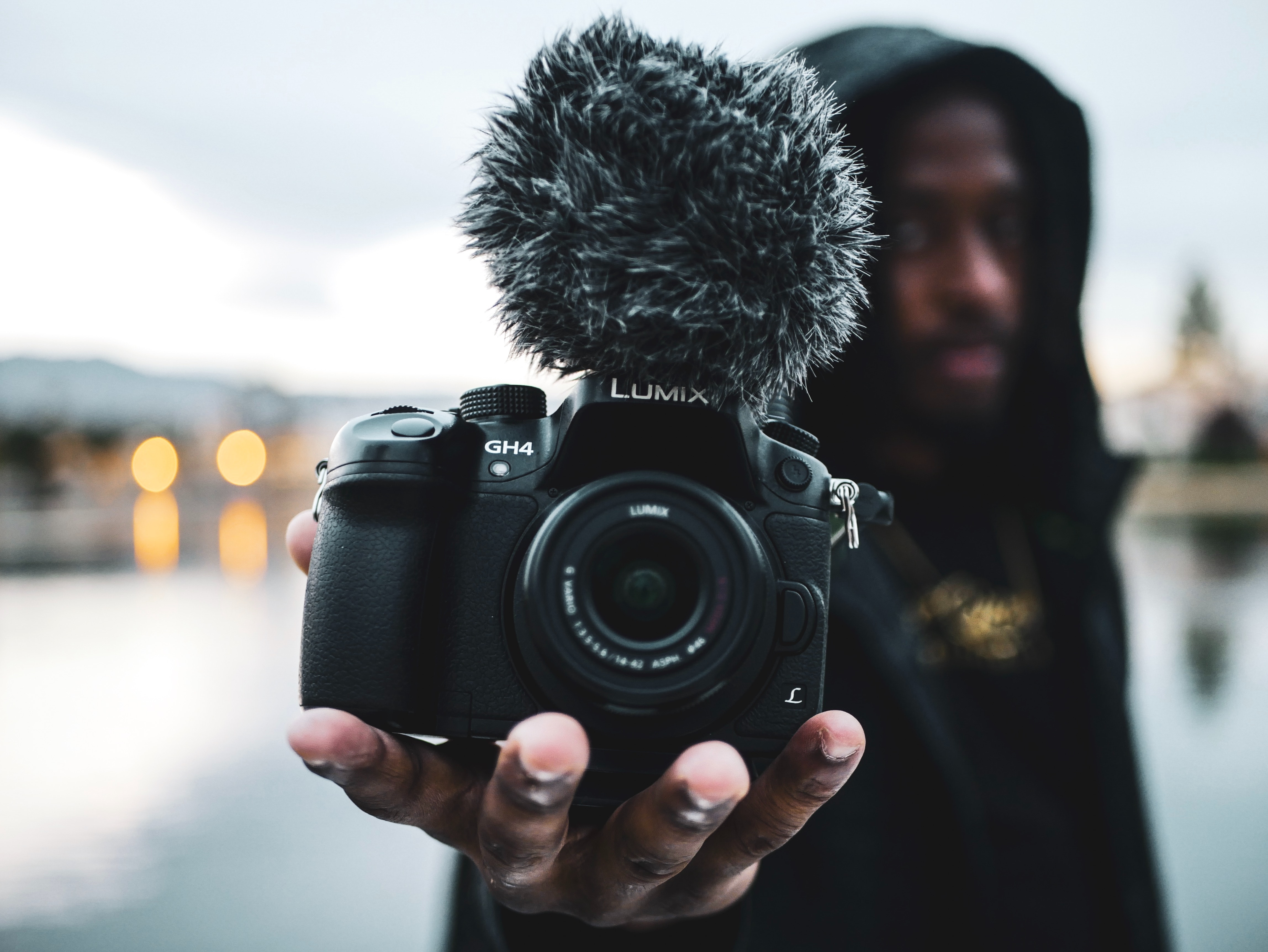 A guy holds a Lumix camera with a mic with a background that is dimmed