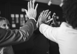 Personer som är affärsklädda gör high five's tillsammans