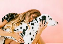 Influencer kramar en dalmatin med en rosa vägg i bakgrunden