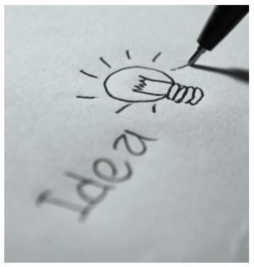 A paper that says 'Idea' on it, with a light bulb that glows next to it
