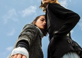 Två influencers i mörka trendiga kläder poserar ner mot marken med en blå himmel ovanför dem